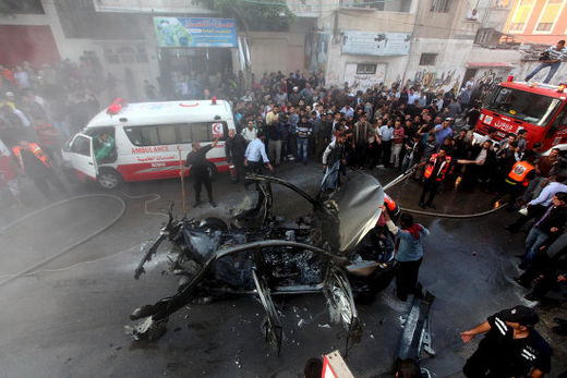 Palestinian firefighters extinguish the car of Ahmad al-Jabari, head of the military wing of the Hamas movement, after it was hit in an Israeli air strike in Gaza City, 14 November