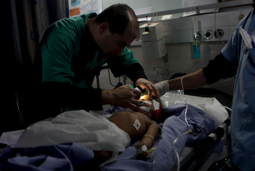 A doctor at Gaza City's al-Shifa hospital uses the light of his mobile phone to check the vital signs of critically-injured Haneen Tafish, a one-year-old from the al-Zeitoun neighborhood on 15 November, the second day of a massive Israeli attack on Gaz