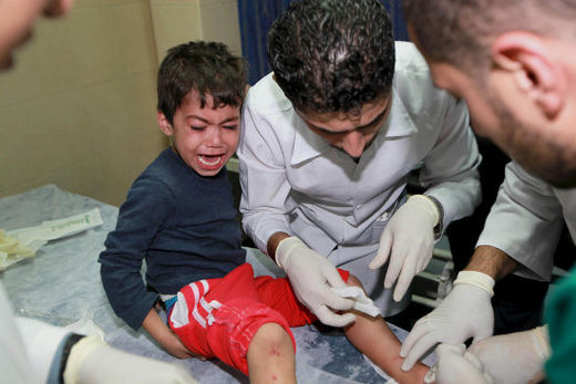 A Palestinian medic treats a wounded boy at Gaza City's al-Shifa hospital following an Israeli airstrike, 14 November