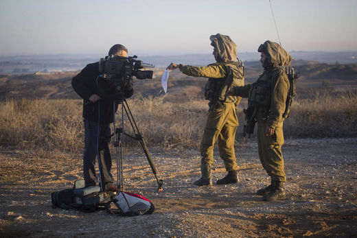 Israeli soldiers display a military order to a cameraman in southern Israel to prevent him from filming Gaza