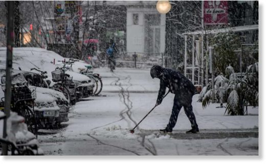 A woman clears snow from the pavement in Hamburg, northern Germany.