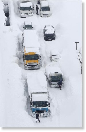 An aerial photo shows cars and trucks buried in snow and stranded on Route 8 in Sakai, Fukui Prefecture, on Wednesday.