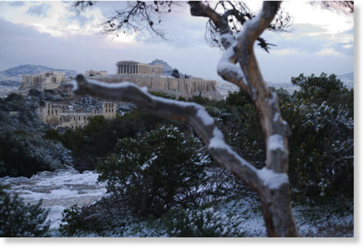 Snow covers a tree in front of the ancient Acropolis hill with the 500BC Parthenon temple, after snow fell in Athens, on Tuesday,